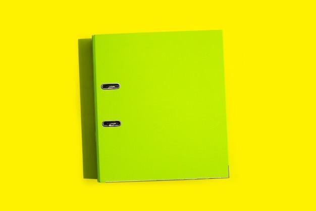Green office folder on yellow