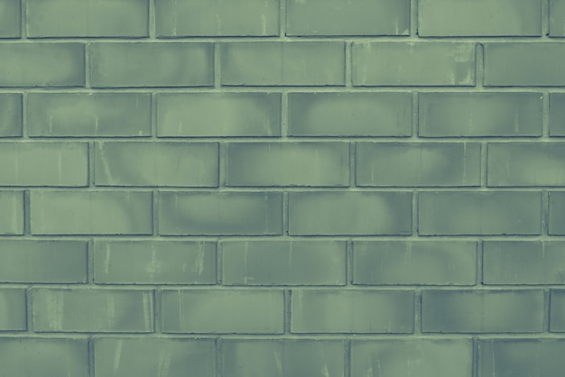 Green old brick wall close-up with stitching. the texture of the stone masonry. brick background for a subject shooting a flat lay. concept of construction and interior design. copy space