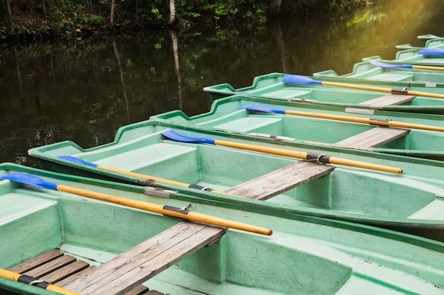 Green old empty boats with wooden oars on the lake closeup.