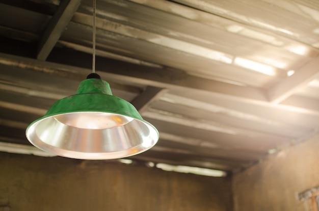 緑の古いランプは、古い亜鉛の中に放棄された家の天井の上にぶら下がっています。