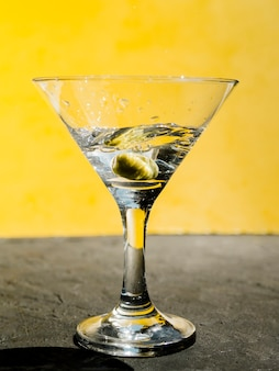 Green olive splashing in martini