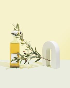 파스텔 노란색과 청록색 배경에 녹색 올리브 나무 가지. 하나의 흰색 3d 개체입니다. 올리브 오일 제품 개념입니다. 자연스러운 하드 라이트 섀도우. 최소한의 음식 장면.