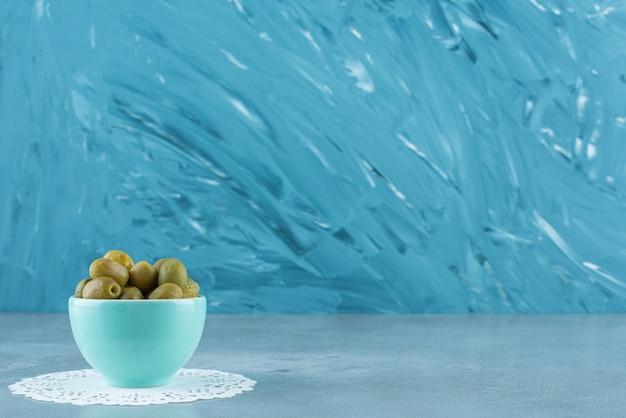Olive verdi in una ciotola su un sottobicchiere, sul tavolo di marmo.