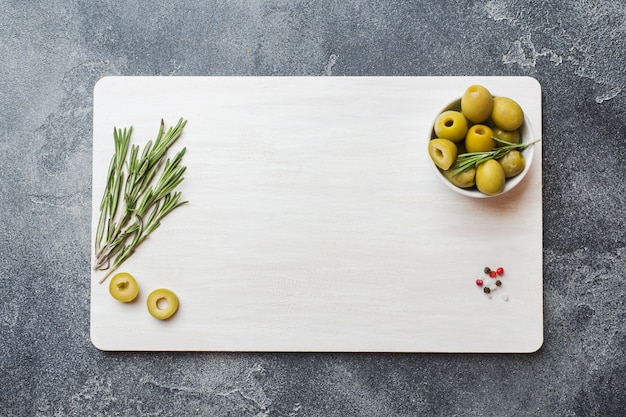 Green olives in bowls and rosemary branches on a white board