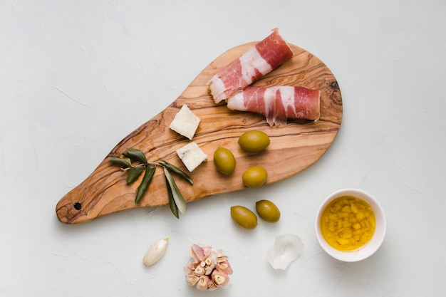 Green olives; cheese; garlic and bacon on wooden chopping board