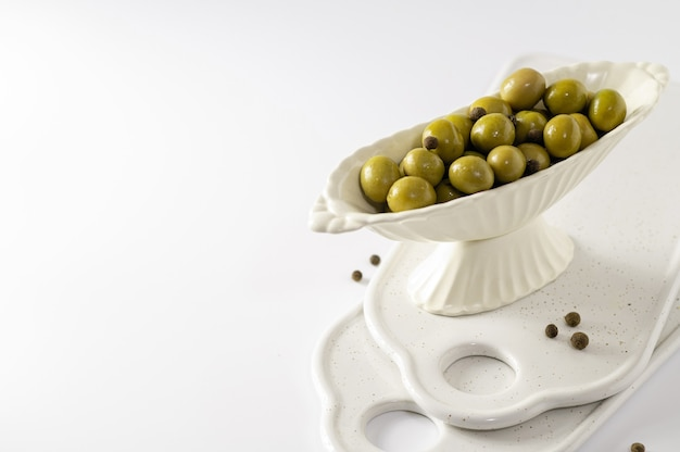 Green olives in decorative crockery on white background, empty space for text