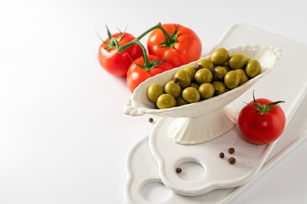 Green olives in a decorative dish with red tomatoes on a white background, empty space for text