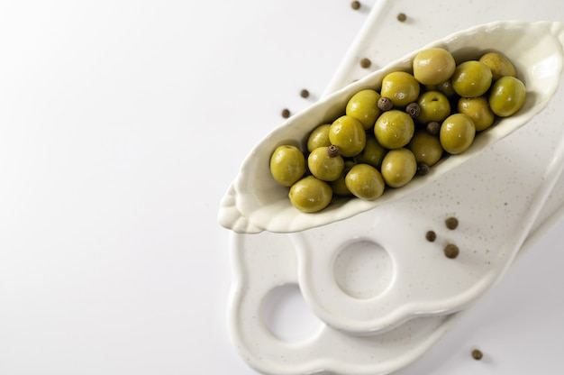 Green olives in decorative dishes on white background, top view, empty space for text