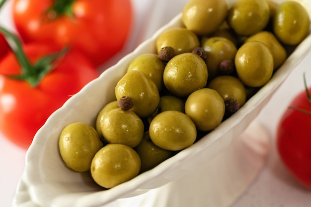 Green olives in decorative dishes with red tomatoes on a white background, large format