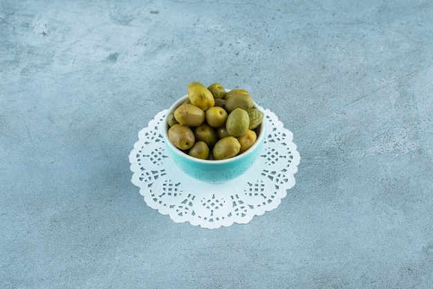 대리석 테이블에 코스터에 그릇에 그린 올리브.