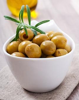 Зеленые оливки в миску.