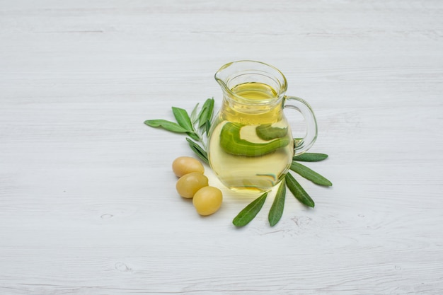 Green olives and olive oil in a glass jar with olive leaves side view on white wood plank