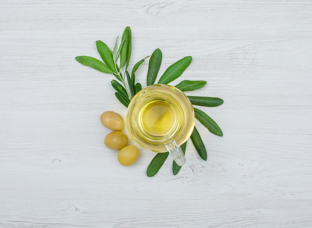 Green olives and olive oil in a glass jar with olive tree branch top view on white wood plank