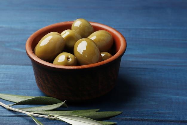 Зеленые оливки на голубом дереве. место для текста.