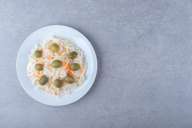 Зеленые оливки на квашеной капусте на тарелке, на мраморном фоне.