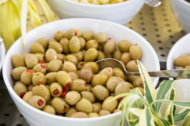 Зеленые оливки фаршированные паприкой на тарелке.