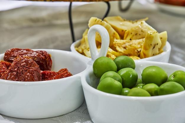 グリーンオリーブ、サンドライトマト、アーティチョークのピクルスをテーブルの皿に盛り付けます。健康的な食事