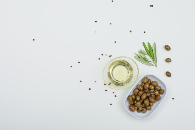 Green olives with a jar of olive oil, spices and olive leaves in a white plate on white, top view.