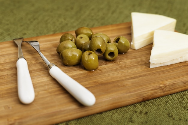 Green olives without seeds and goat cheese on wooden surface