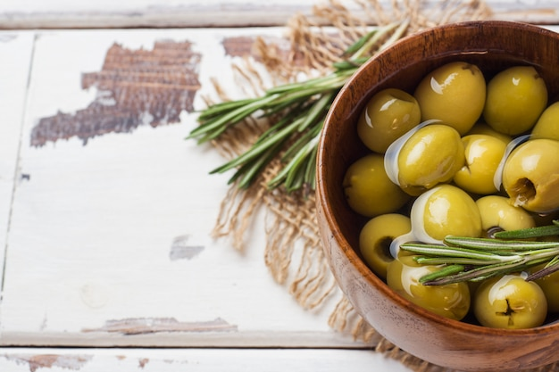 Green olives in wooden bowls on wooden table
