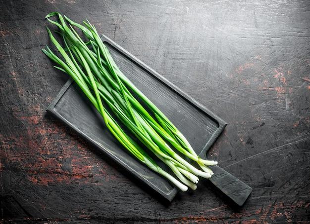Зеленый лук на разделочной доске на темном деревенском столе