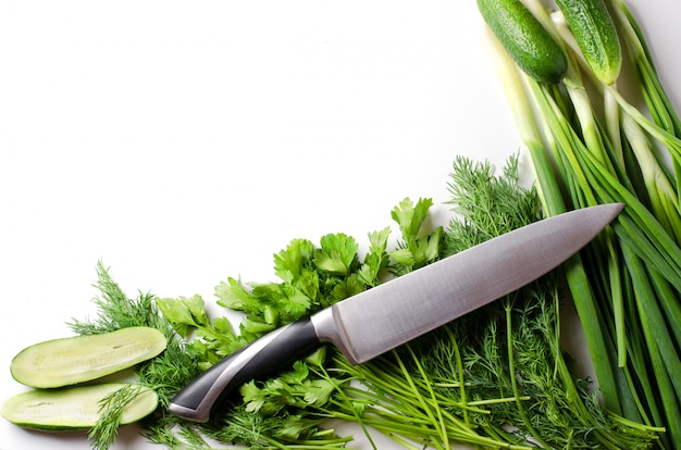 Green onions, dill, parsley, cucumbers, kitchen knife on white