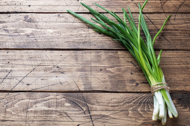 Green onions or shallots on a wooden