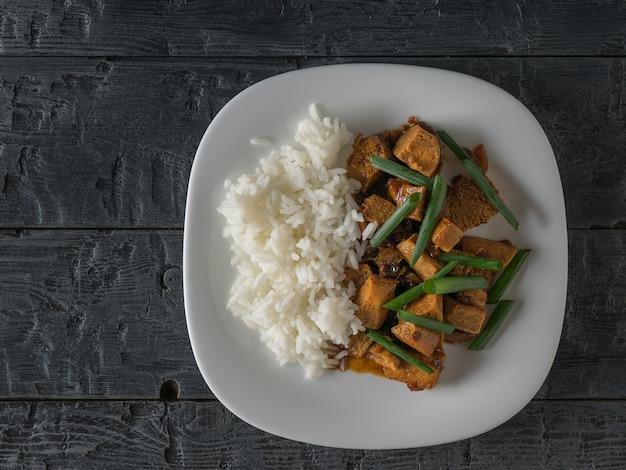 Зеленый лук с жареным сыром тофу и рисом на деревянном столе. плоская планировка. вегетарианское азиатское блюдо.