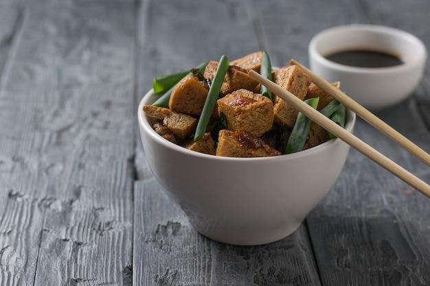Зеленый лук с тушеным тофу в миске на деревянном столе