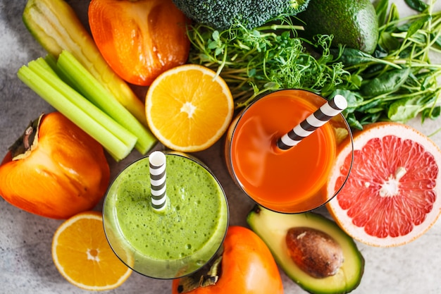 Green and orange detox smoothie in glass. ingredients for detox smoothie background. healthy food concept.
