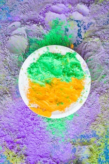 Green and orange holi powder on plate over the backdrop