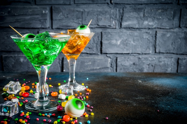 Green, orange martini cocktail with ice cubes and a decor of marshmallow eyes