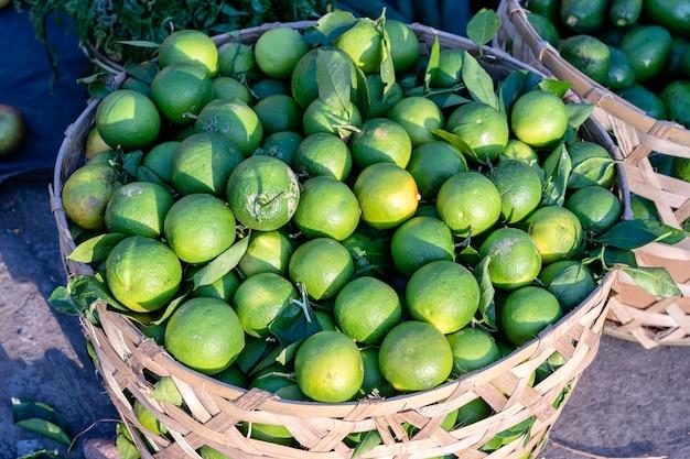 インドネシア、バリ島、ウブドの伝統的なストリートマーケットの竹または木製バスケットのグリーンオレンジをクローズアップ