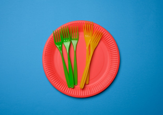 Green, orange plastic forks and empty red paper disposable plates, set