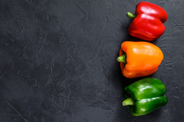 Green, orange and red bell peppers. black background. top view. space for text.