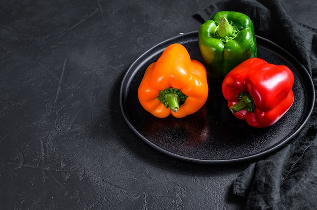 Green, orange and red bell peppers on a plate.