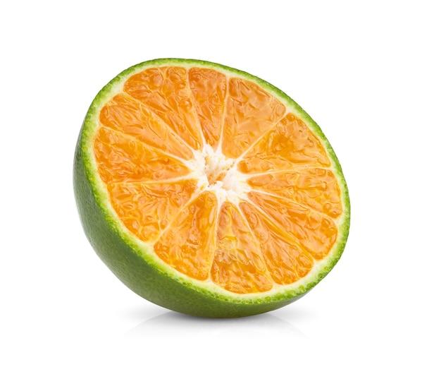 白い表面でスライスされ分離されたグリーンオレンジタンジェリン