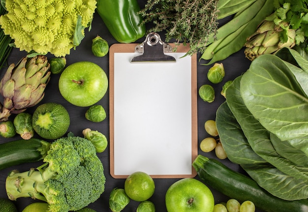 Green organic vegetables and blank page in the center
