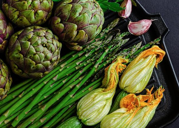 Зеленые органические овощи на темном столе. плоская планировка