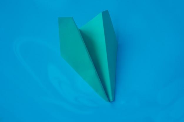 파란색 배경에 녹색 종이 접기 비행기