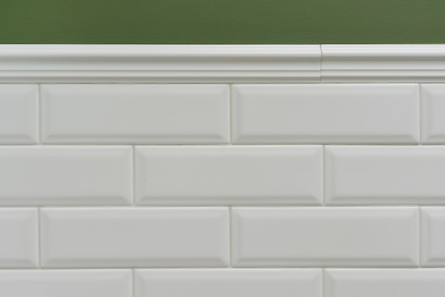 Green painted wall, part of the wall is covered tiles small white glossy brick