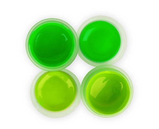 白い背景の上の瓶の中の緑の塗料
