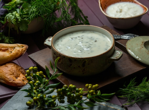 A green pan of yogurt soup with herbs