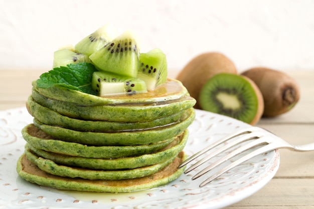 Green pancakes with honey and kiwi. on a light background.