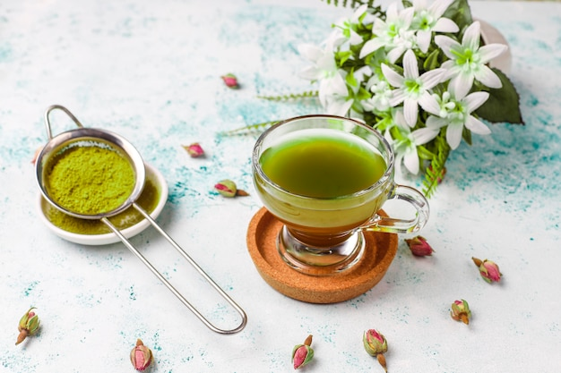 Green pancakes with matcha powder with red jam on light table