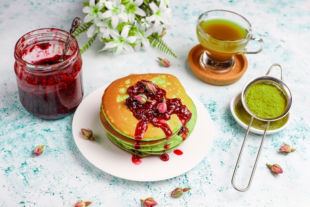 Green pancakes with matcha powder with red jam on light