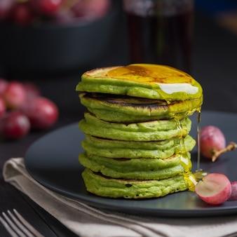 抹茶またはほうれん草、はちみつ、赤ブドウを添えたグリーンパンケーキ。スーパーフードの食材を使ったヘルシーな朝食のアイデアとレシピ。暗い背景。