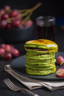 Green pancakes with matcha tea or spinach, dressed honey and red grapes