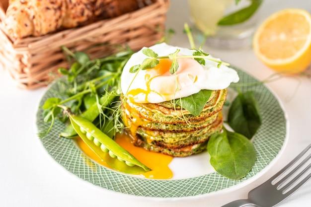 ほうれん草とポーチドエッグのグリーンパンケーキ。おいしい健康的なヨーロッパの朝食。