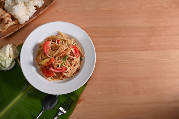 Green papaya salad or som tum in plate .thai food concept. top view
